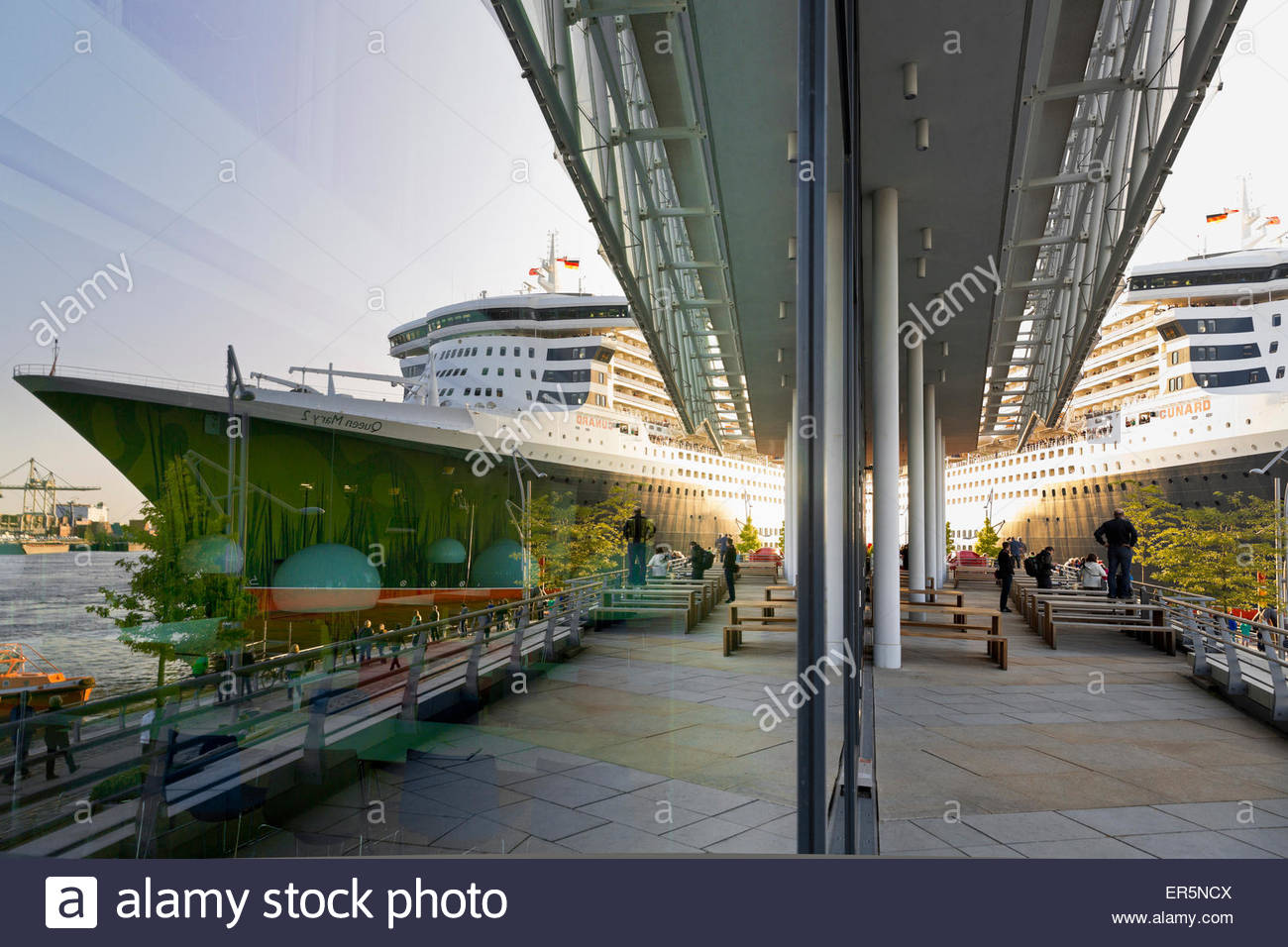 Queen Mary 2 at Chicagokai, reflection in the facade of the Unilever building Hamburg Cruise Center, Hamburg, Germany - Stock Image