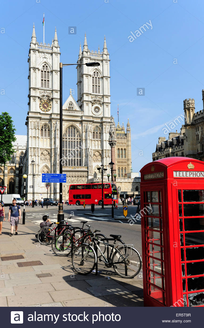 Red telephone box in front of Westminster Abbey, UNESCO world cultural heritage site, church in the City of Westminster, - Stock Image