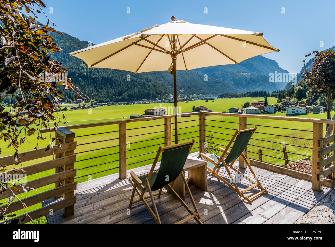 Deckchairs and sunshade on a terrace, lake Achensee and Achenkirch in background, Tyrol, Austria - Stock Image