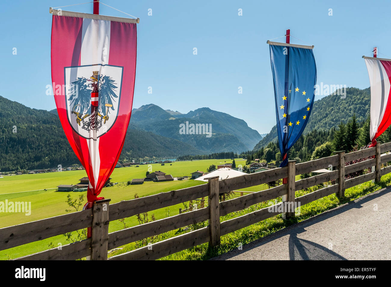 Flags at a fence, lake Achensee and Achenkirch in background, Tyrol, Austria - Stock Image