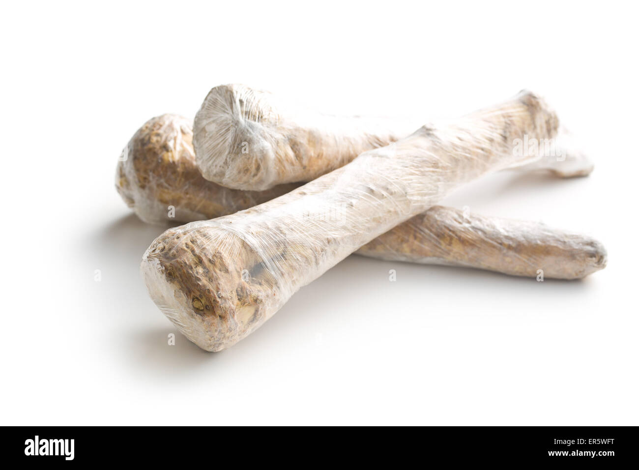 horseradish wrapped in foil on white background - Stock Image