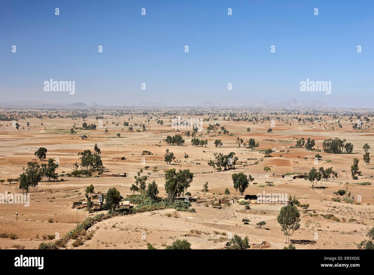 Fields and farmer huts, Gheralta mountains in background, Feraywi, Tigray region, Ethiopia - Stock Image