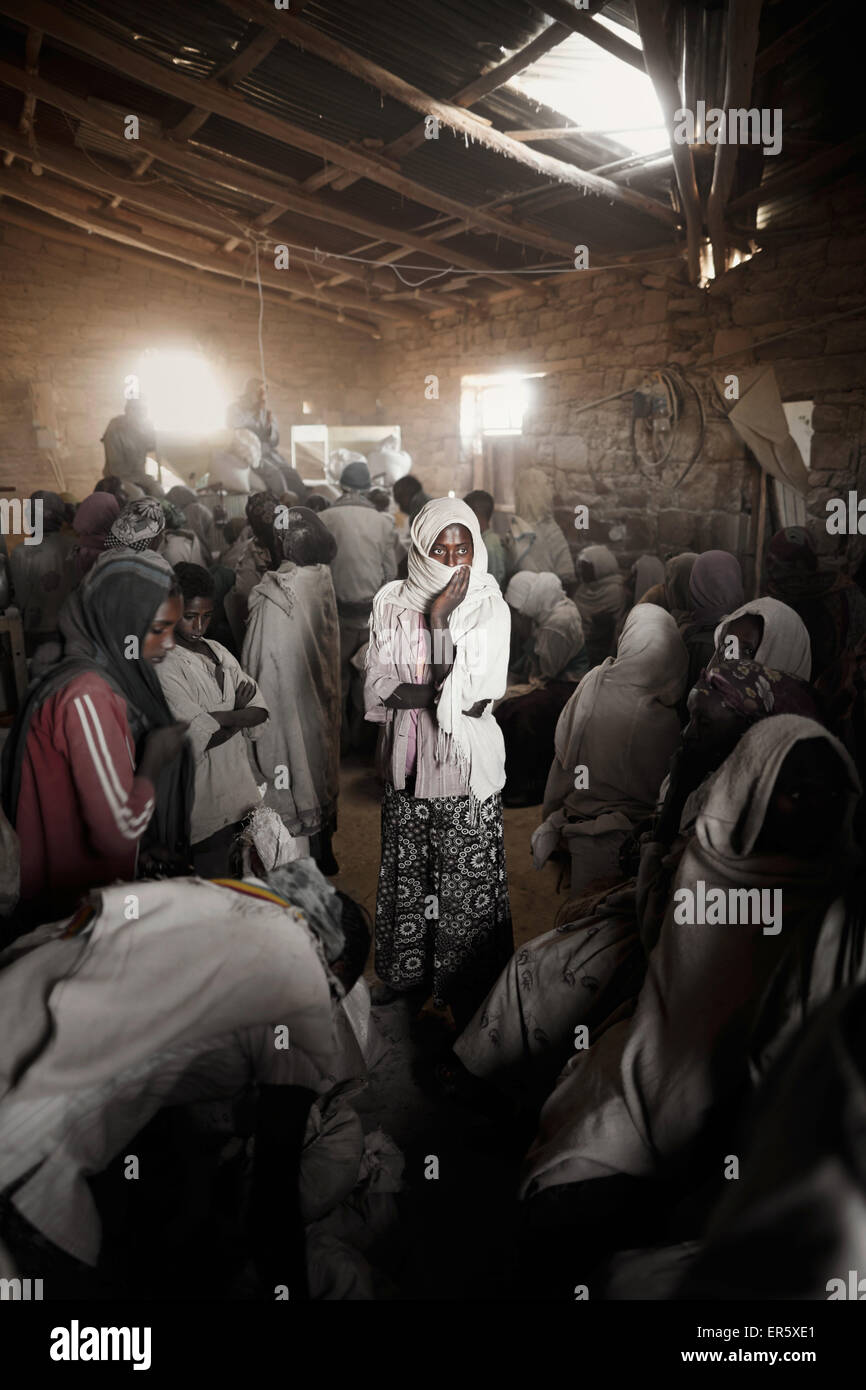 Young women waiting inside a grain mill, Feraywi, Gheralta Area, Tigray Region, Ethiopia - Stock Image