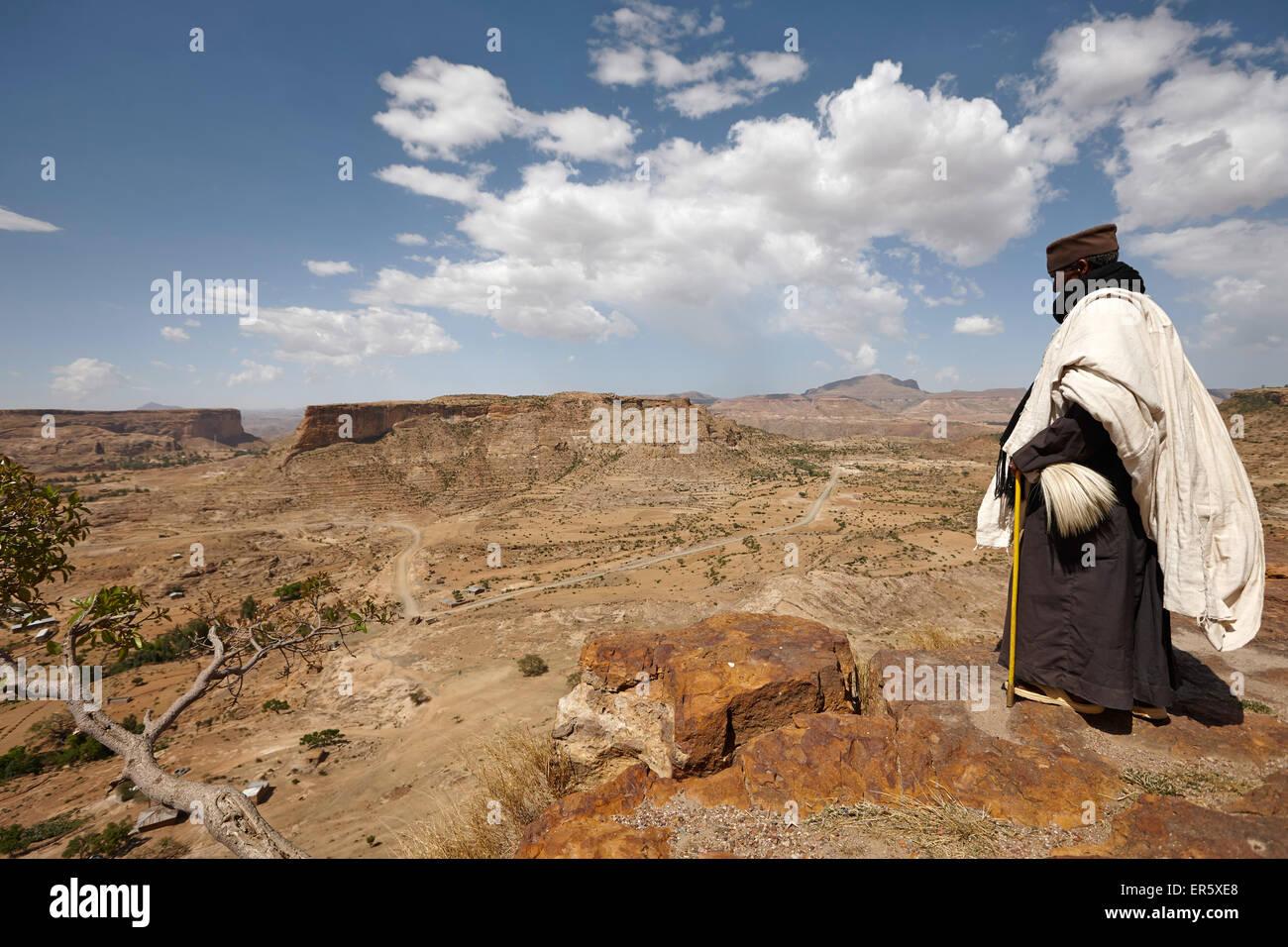 Priest looking over scarp at monastery Debre Damo, near Adigrat, Tigray Region, Ethiopia - Stock Image