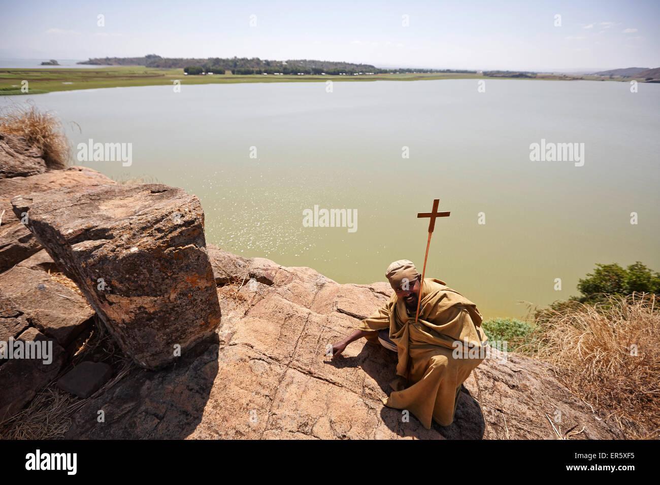 Monk crouching at resting place of Saint Mary, Tana Cherkos monastery island, Lake Tana, Amhara region, Ethiopia - Stock Image