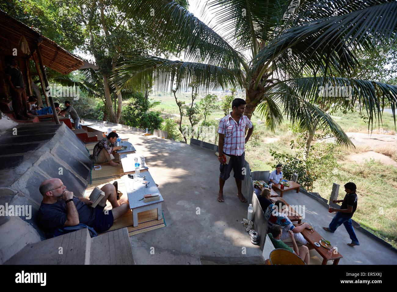 Guests on terrace of a restaurant, Tungabhadra river, Hampi, Karnataka, India - Stock Image