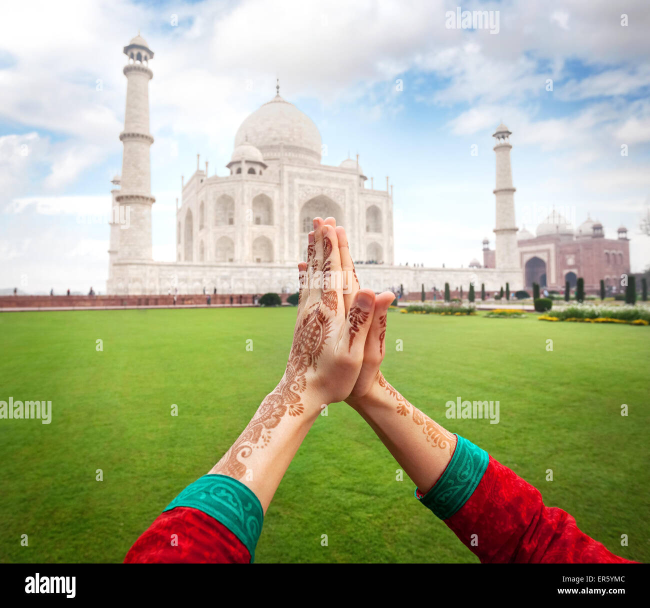 Woman hands with henna painting in Namaste gesture near Taj Mahal in Agra, Uttar Pradesh, India - Stock Image