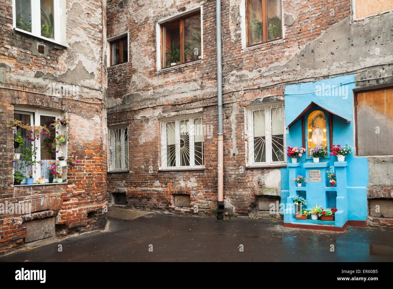 Blue colored shrine with flowers in a bullet-ridden courtyard of an apartment building damaged in war, Warsaw - Stock Image