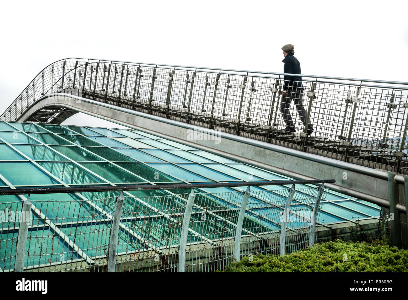 Man ascends a metal bridge over a glass roof at the Warsaw University Library garden, designed by Irena Bajerska Stock Photo