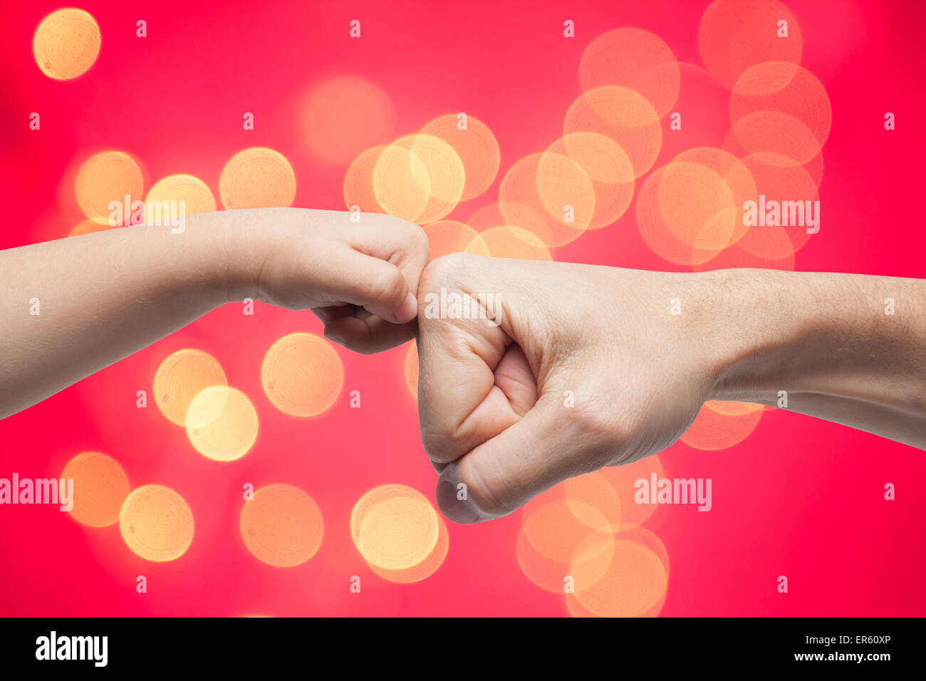 father and son punching fists for agreement on yellow christmas lights and red background. - Stock Image