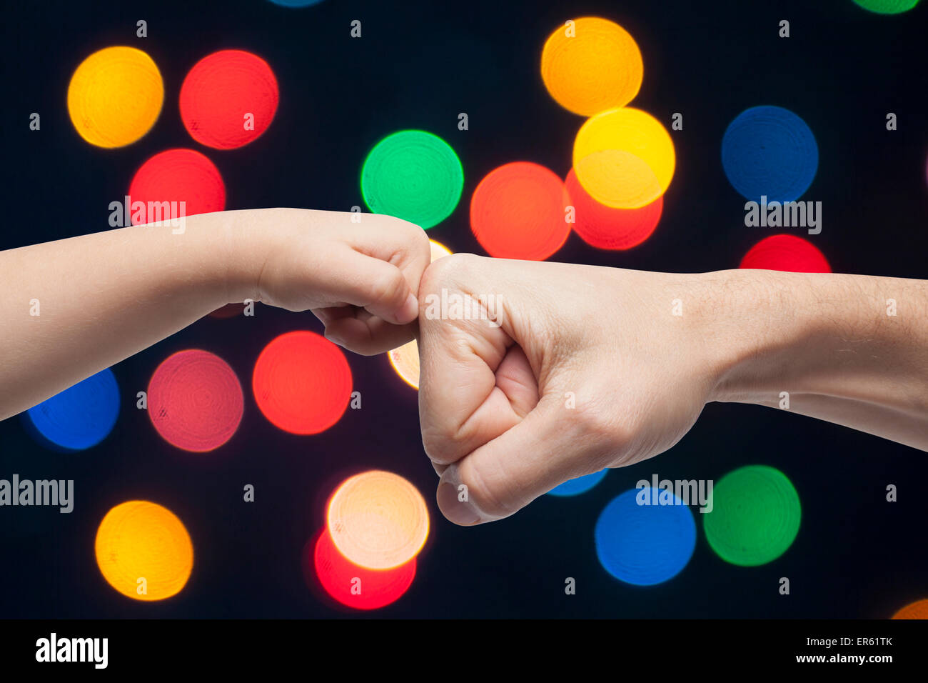 father and son punching fists for agreement on multicolored christmas lights background. - Stock Image