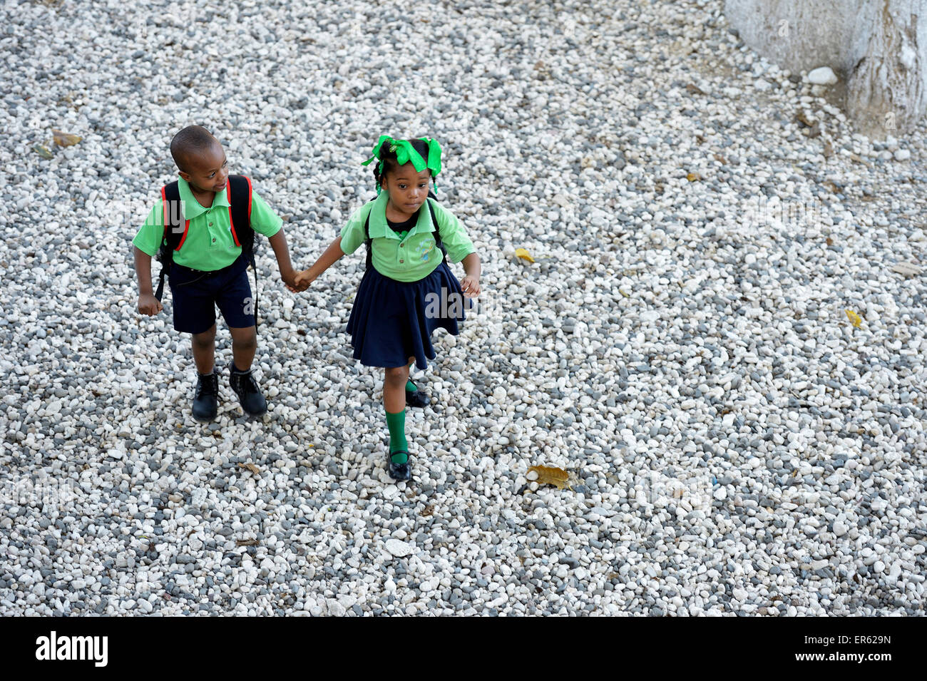 Boy and girl, siblings, holding hands on the way to the nursery school, Port-au-Prince, Ouest Department, Haiti - Stock Image