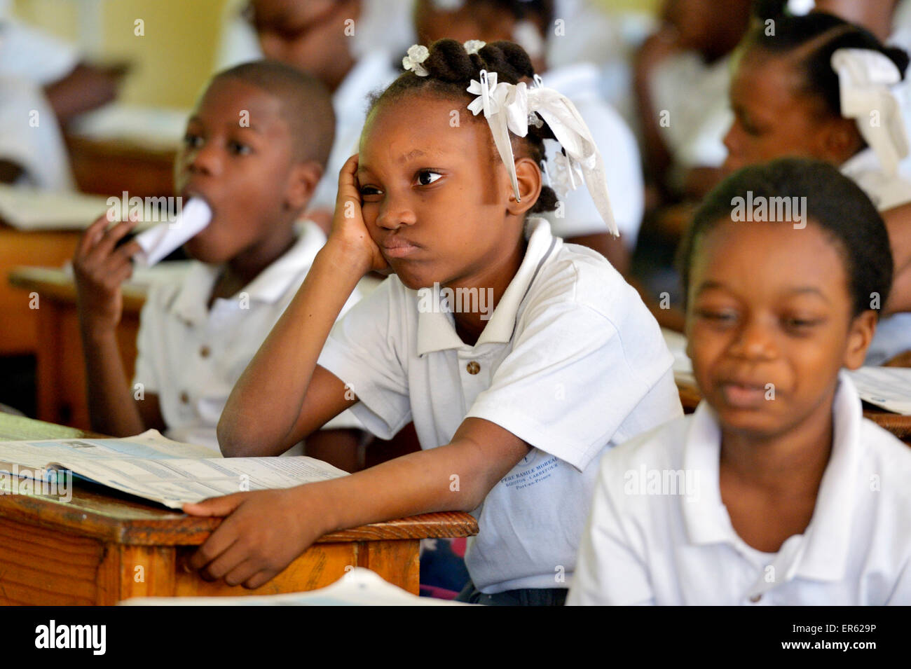 Schoolgirl with sullen facial expression during class, Port-au-Prince, Ouest Department, Haiti - Stock Image