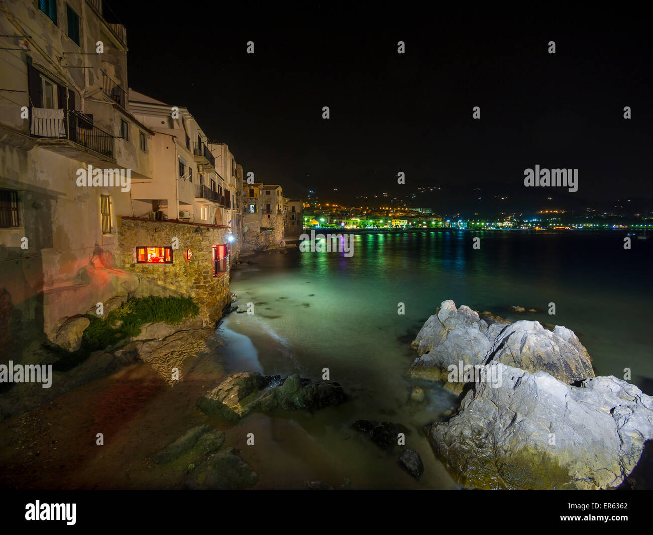 Medieval houses on the beach of Cefalu at night, Cefalu, Province of Palermo, Sicily, Italy - Stock Image
