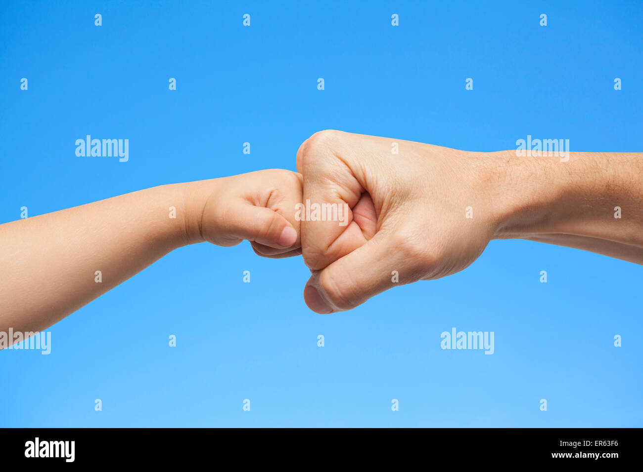 father and son punching fists/hands for agreement on blue sky background. - Stock Image