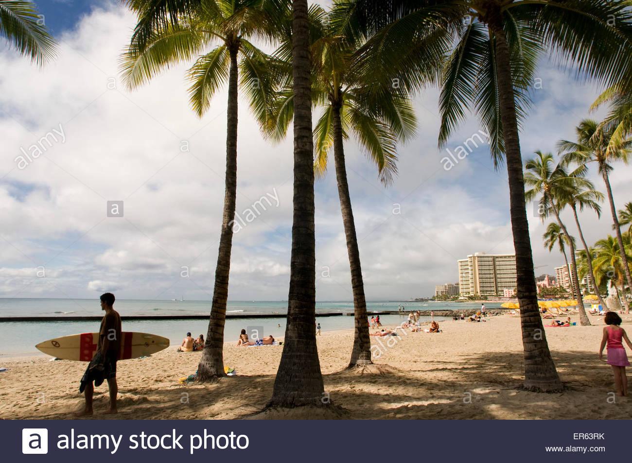 Surfer on the famous Waikiki Beach. Kalakaua Avenue. O'ahu. Hawaii. Located on the south shore of Honolulu, - Stock Image