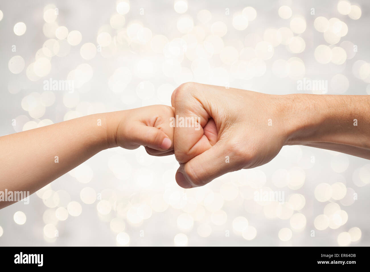 father and son punching fists for agreement on beautiful christmas lights background. - Stock Image