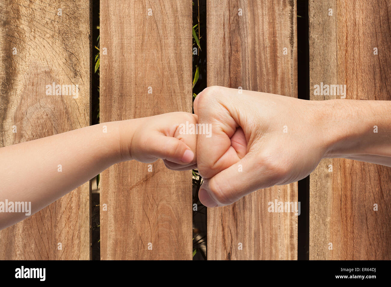 father and son punching fists/hands for agreement over a wooden background - Stock Image
