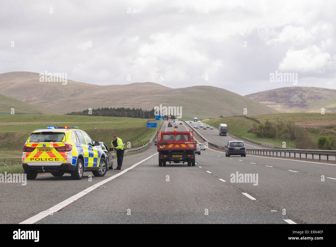 Motorist pulled over by the side of southbound M74 motorway by police officer in patrol car - Scotland, UK - Stock Image
