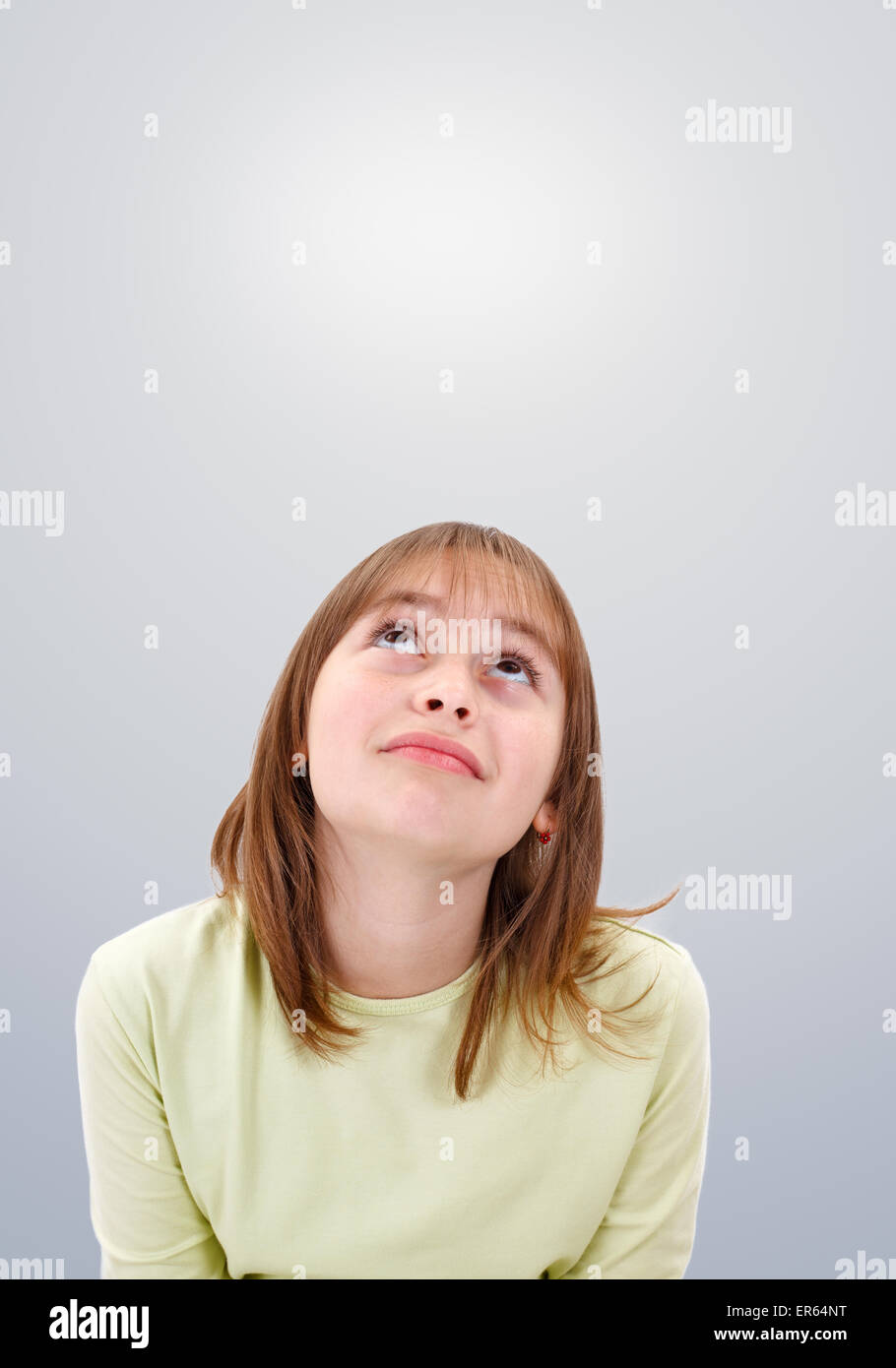 Teenager girl looking up dreamily to copy space - Stock Image