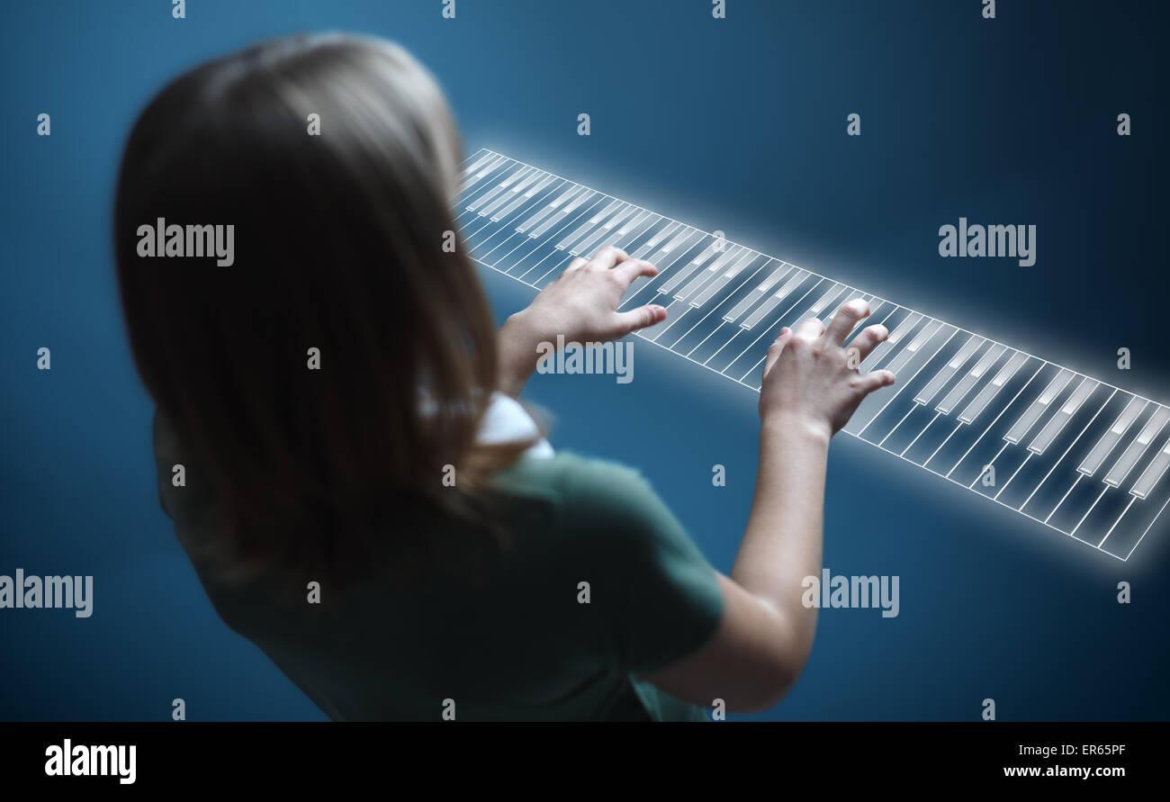 Young girl playing music on virtual piano keyboard Stock Photo