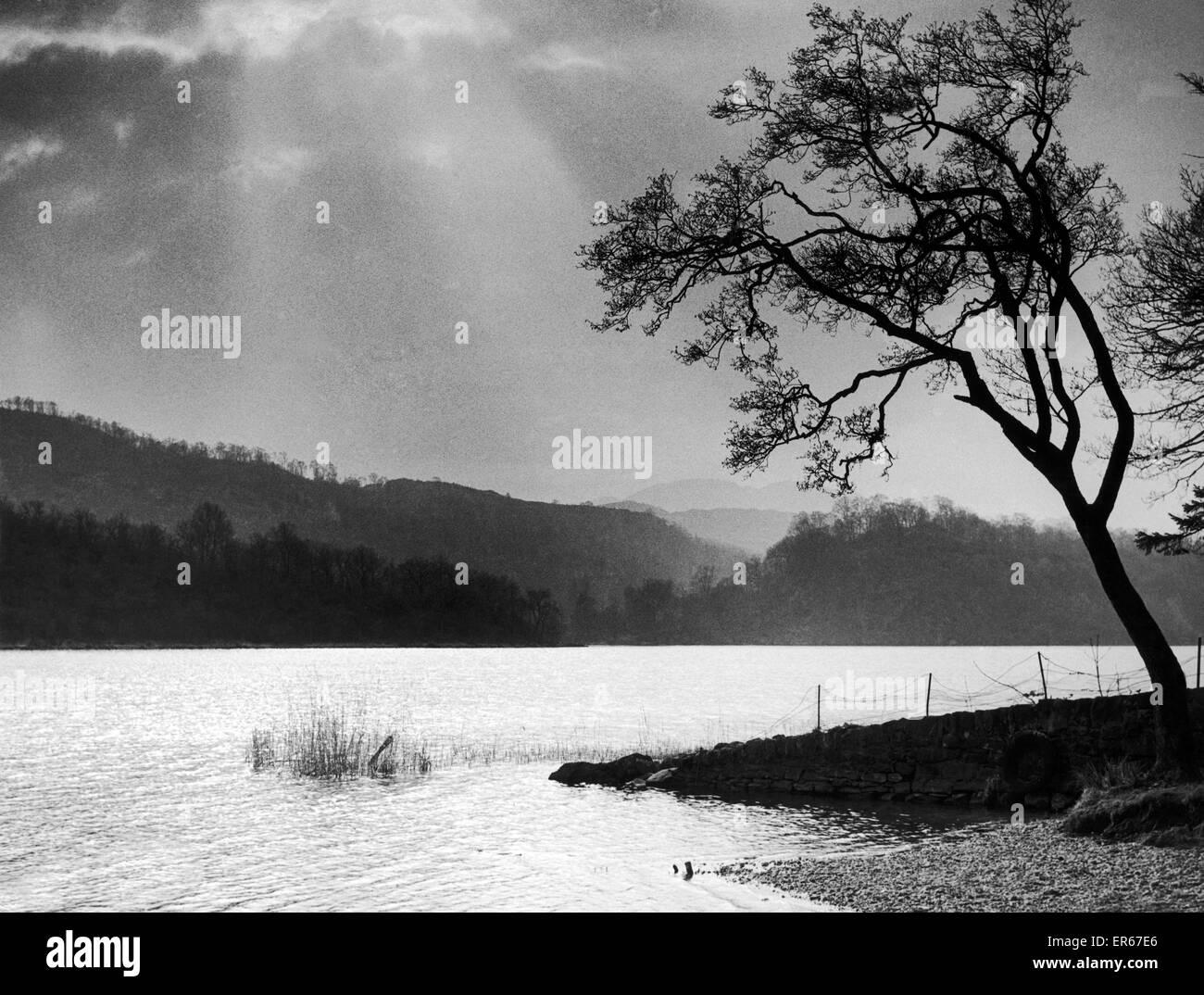 The sun breaks through a heavy sky over Loch Ard near Aberfoyle 14th March 1953 - Stock Image