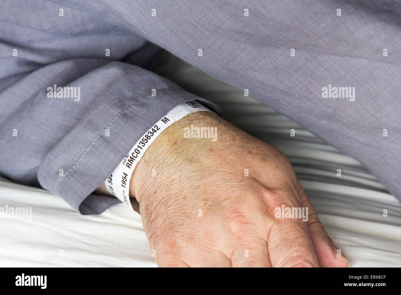 Close up of the arm of a middle aged  man in grey pyjamas in bed with a hospital patient ID wristband visible on - Stock Image