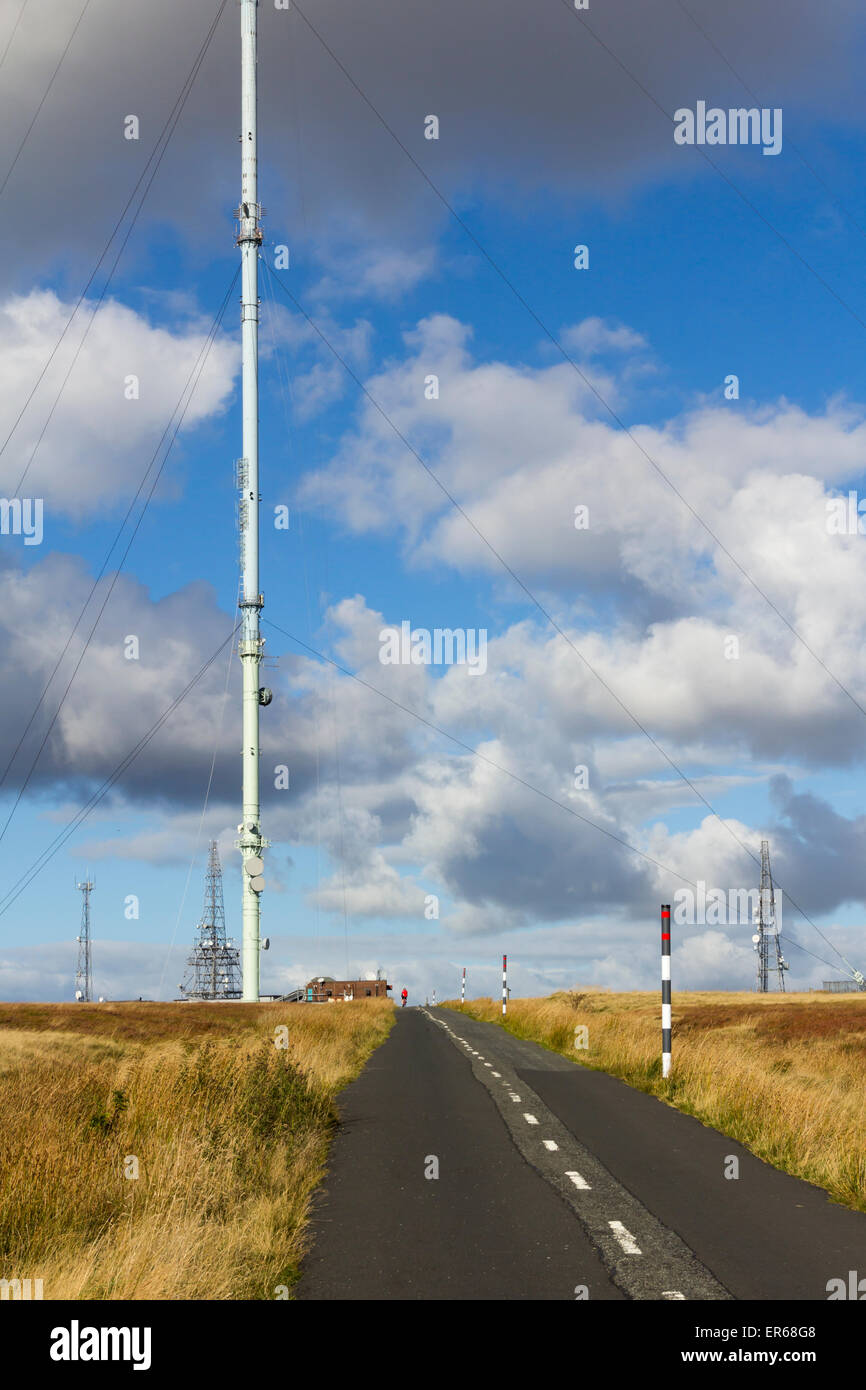 Winter Hill TV transmitter mast on the top of Rivington Moor, Bolton, Lancashire with a solitary cyclist cycling Stock Photo