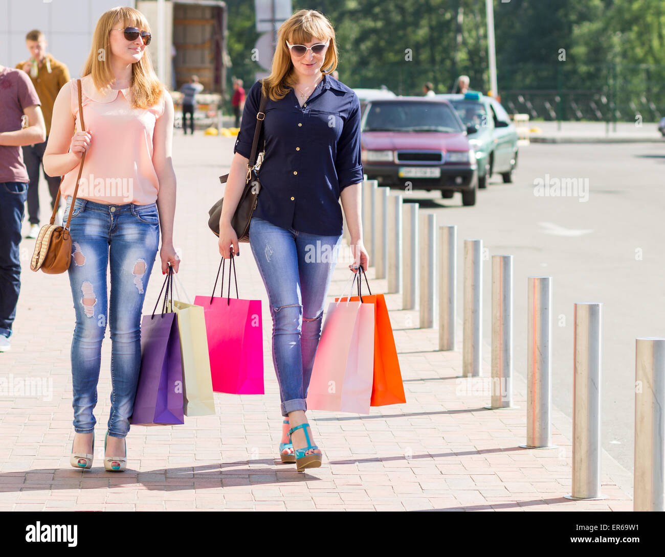 Young smiling pretty women with shopping bags near parking. Twin shopping sisters walking in street at summer day - Stock Image