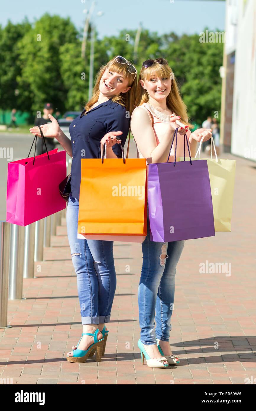 Young twin girls having fun with laughing holding shopping bags. Pretty caucasian women standing near parking waiting - Stock Image