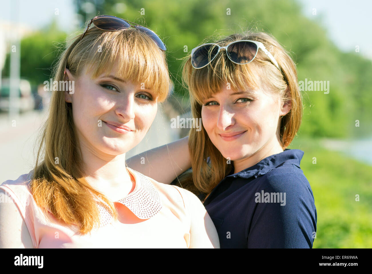 Pretty twins girls having fun at outdoor summer park. Young twin women looking in camera near river