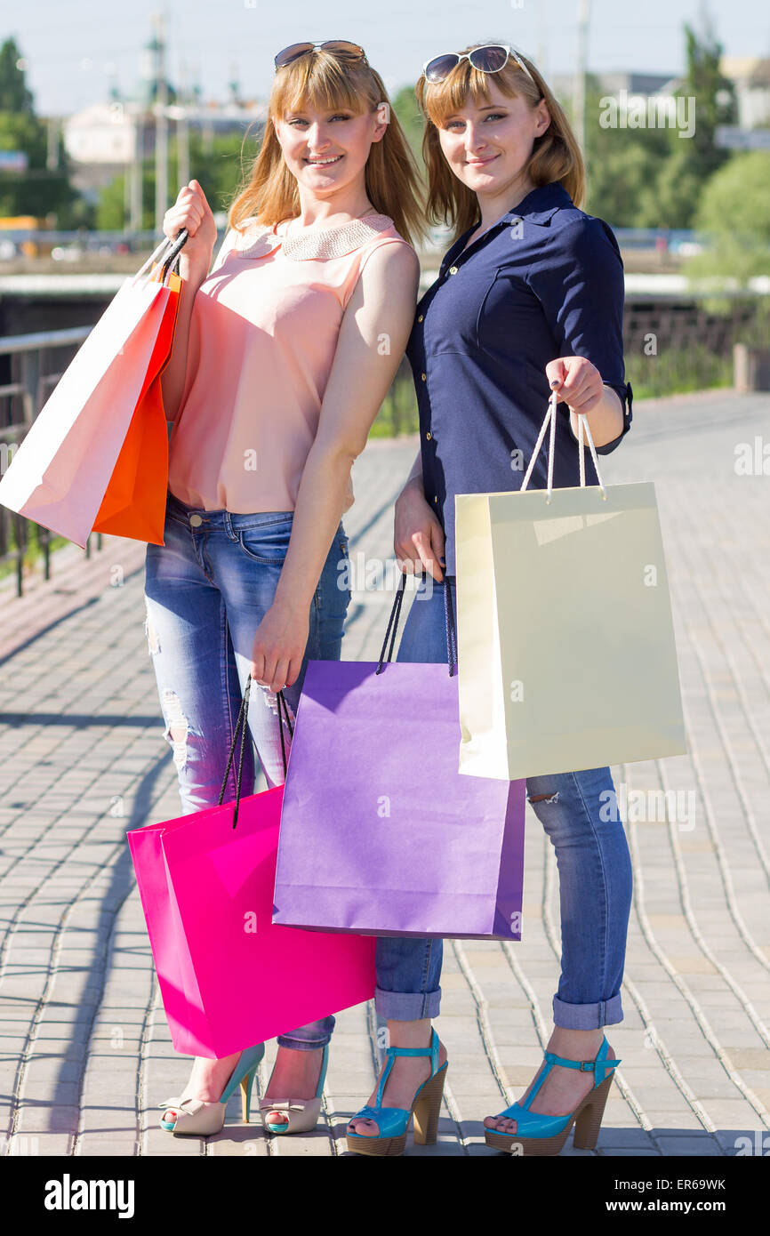 Young twins girls have fun holding their shopping bags. Two women shopping at summer day in city - Stock Image