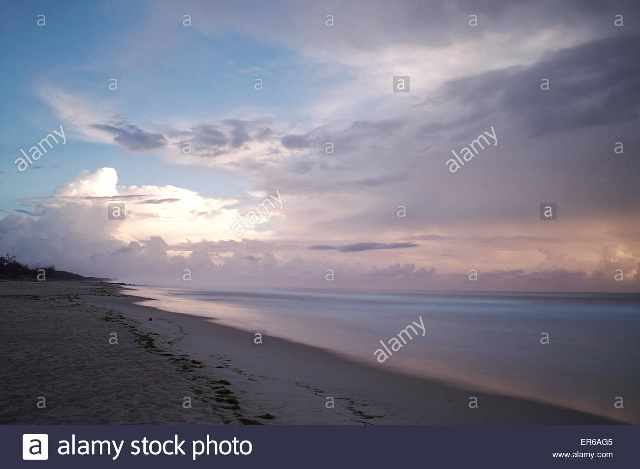 New Year's Day morning 2015, looking north up the beach as the sun rises over the Pacific Ocean from behind - Stock Image