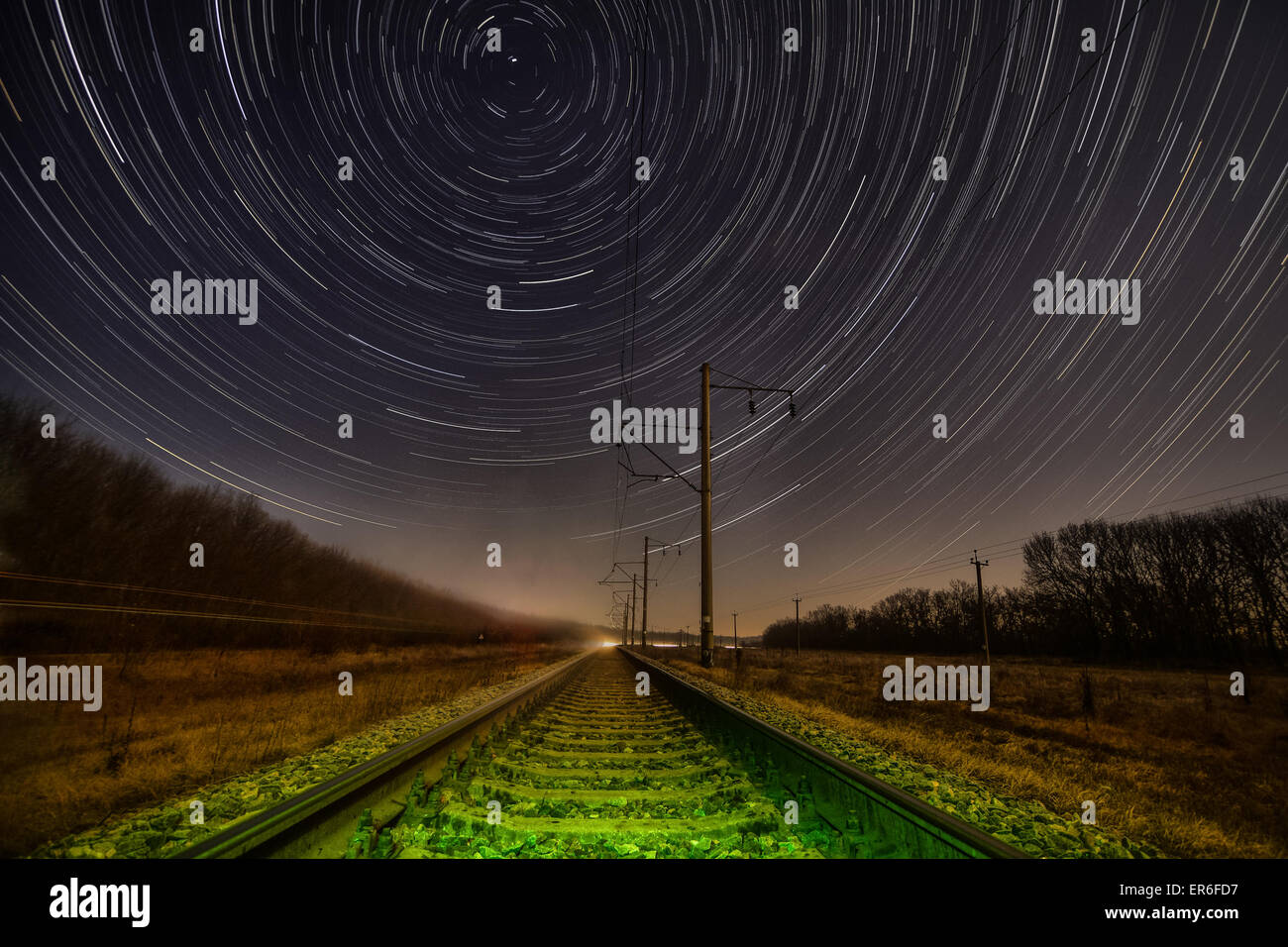 Night rails -green light train way with motion stars, stratrails skyes - Stock Image