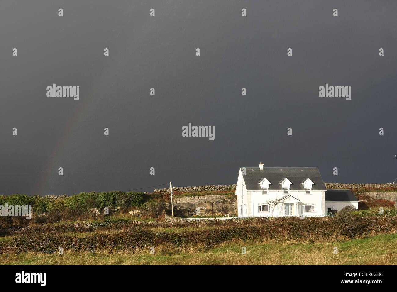 typical Irish cottage during a rainstorm with rainbow.Inishmore,Aran Islands,Ireland,Europe - Stock Image