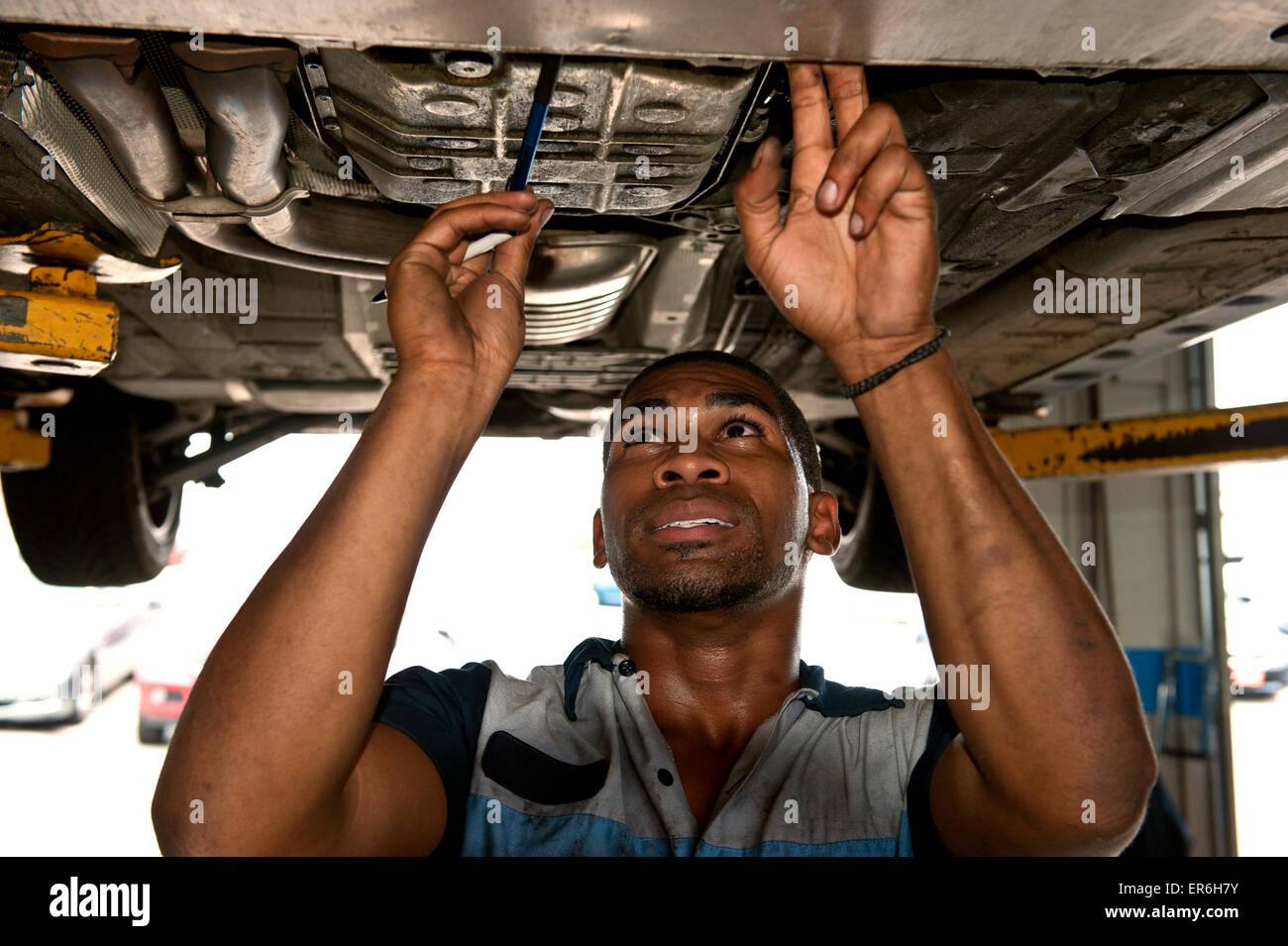 Good Looking African American Mechanic Checking Out Under Carriage of Vehicle - Stock Image