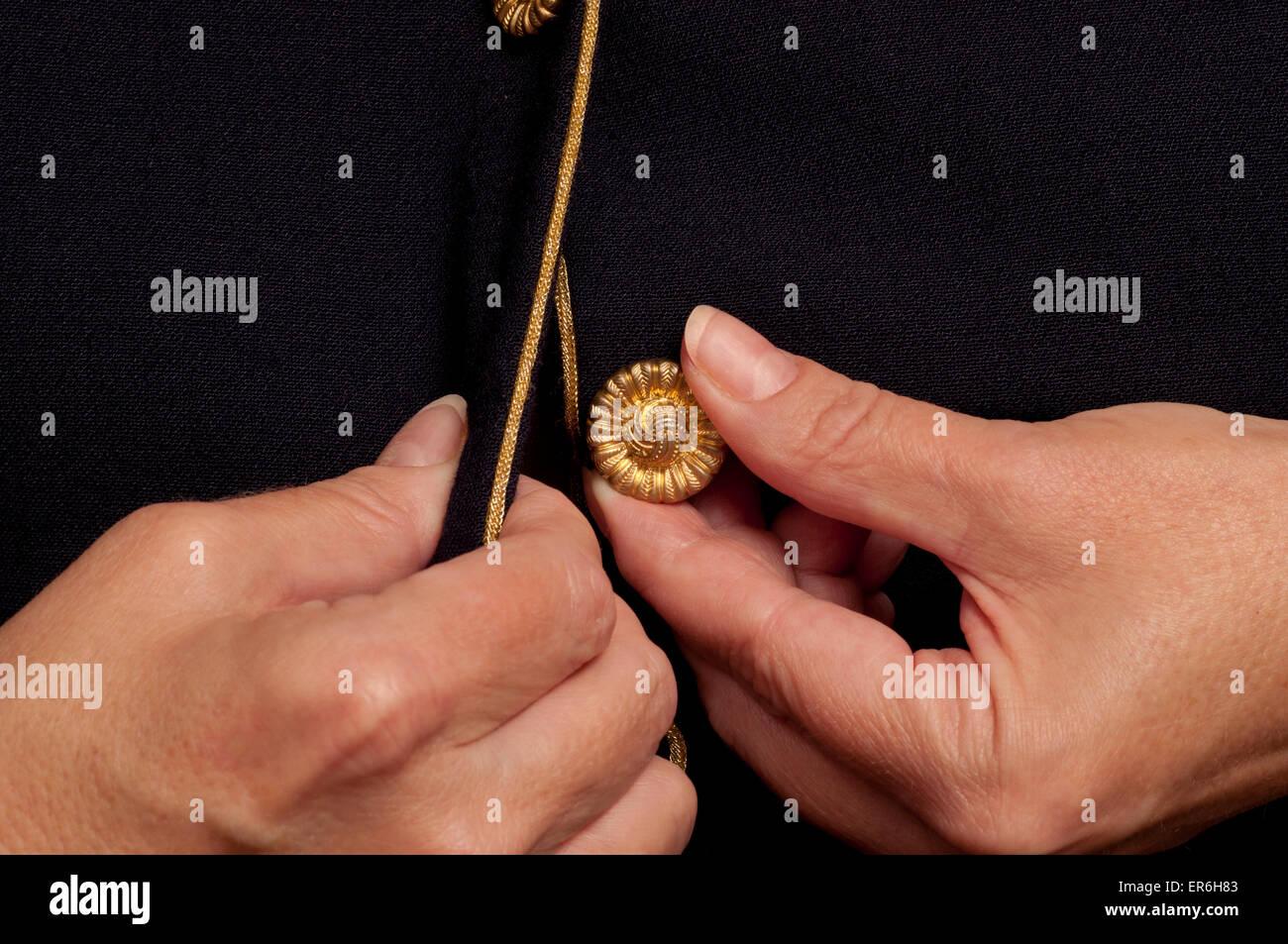 Woman with arthritis trying to button a button with painful hands. - Stock Image