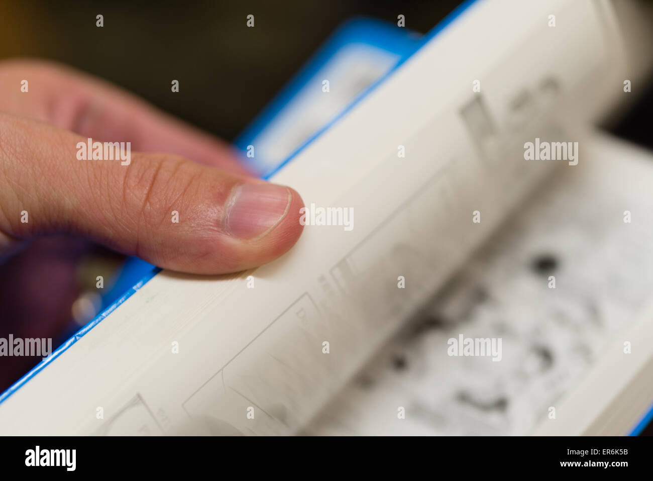 A close up of a hand flipping through the pages of a paperback book. - Stock Image