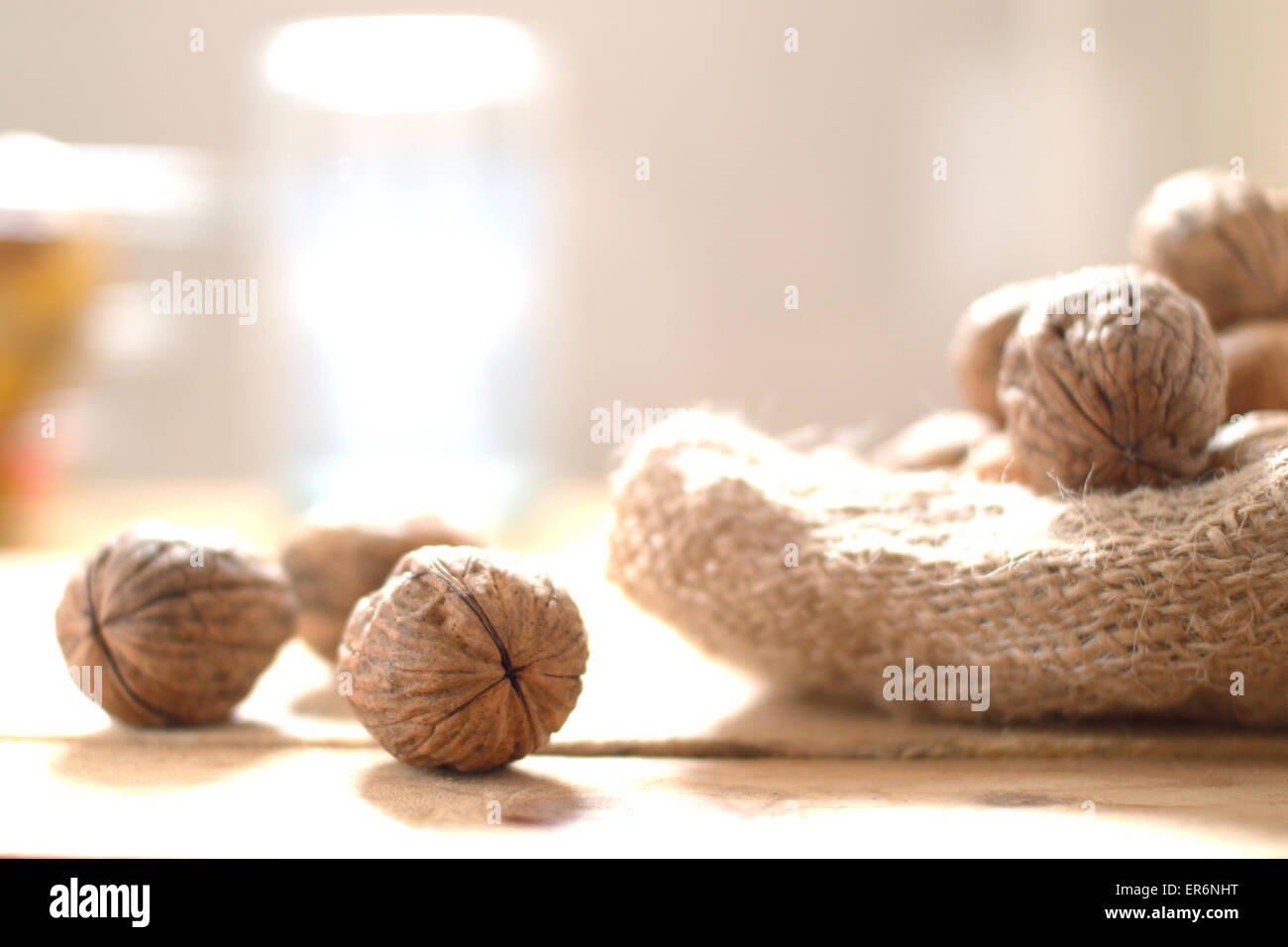 Some walnuts scattered on a sack on a rustic wooden kitchen. - Stock Image