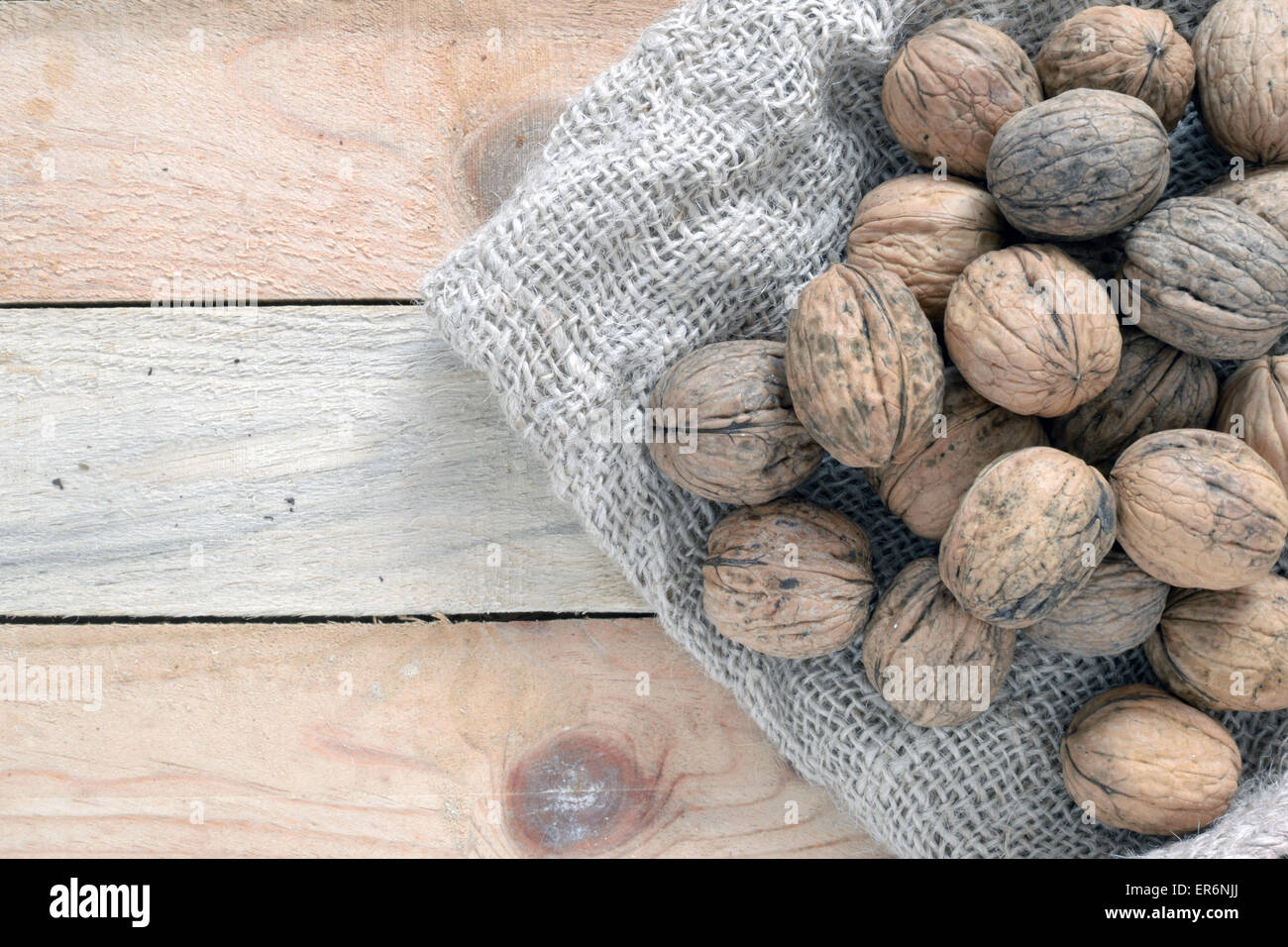 Some walnuts on a sack on a wooden table of a rustik kitchen. - Stock Image