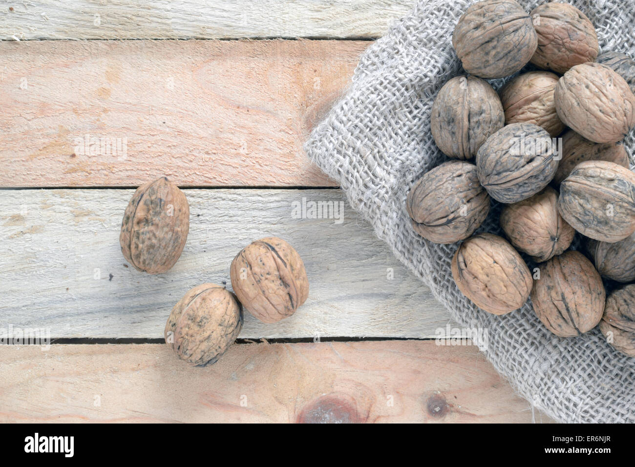 Some walnuts scattered on a table and a sack in a rustic wooden kitchen, top view - Stock Image