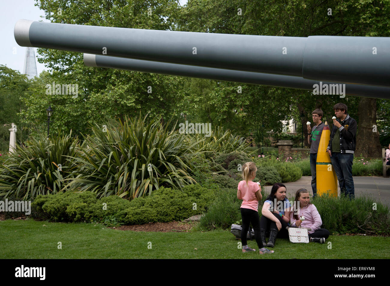 Lambeth. Imperial War Museum. Young people eat ice creams next to two 15' naval guns outside the museum - Stock Image
