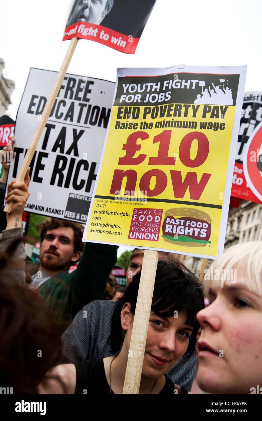 London Anti Austerity Protest. A young woman holds a placard saying 'End poverty pay. £10 now'. - Stock Image
