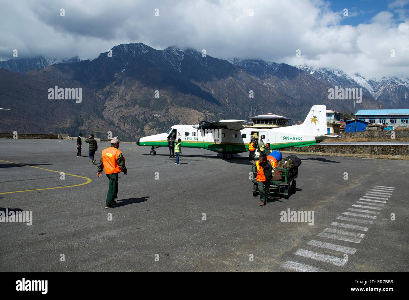 Ground crew unloading baggage from a Tara Air Dornier 228 at Lukla Airport, Nepal. - Stock Image