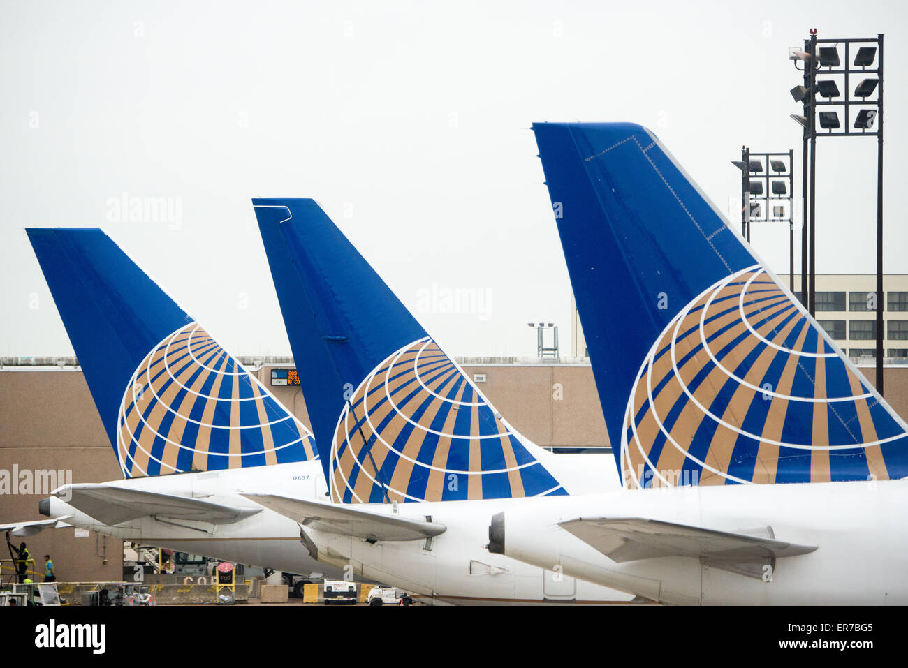 a row of three tails of united airlines planes lined up at the gate