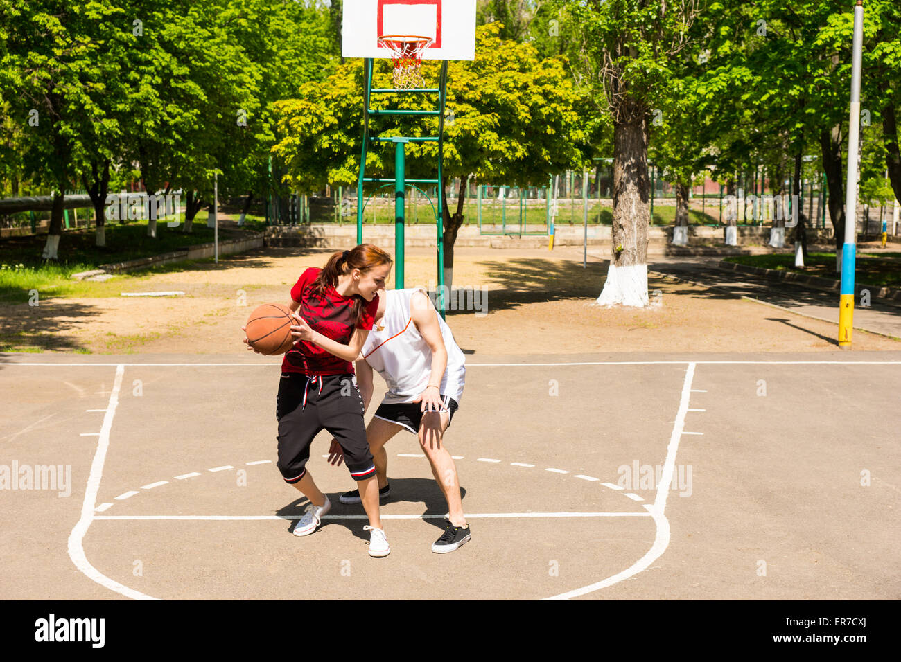 Young Athletic Couple Playing Basketball Together On Outdoor Court