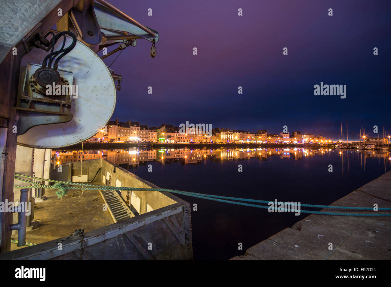Cherbourg, France. the Back of a fishing boat anchored at the lagoon at night. Lit buildings and evening sky in - Stock Image
