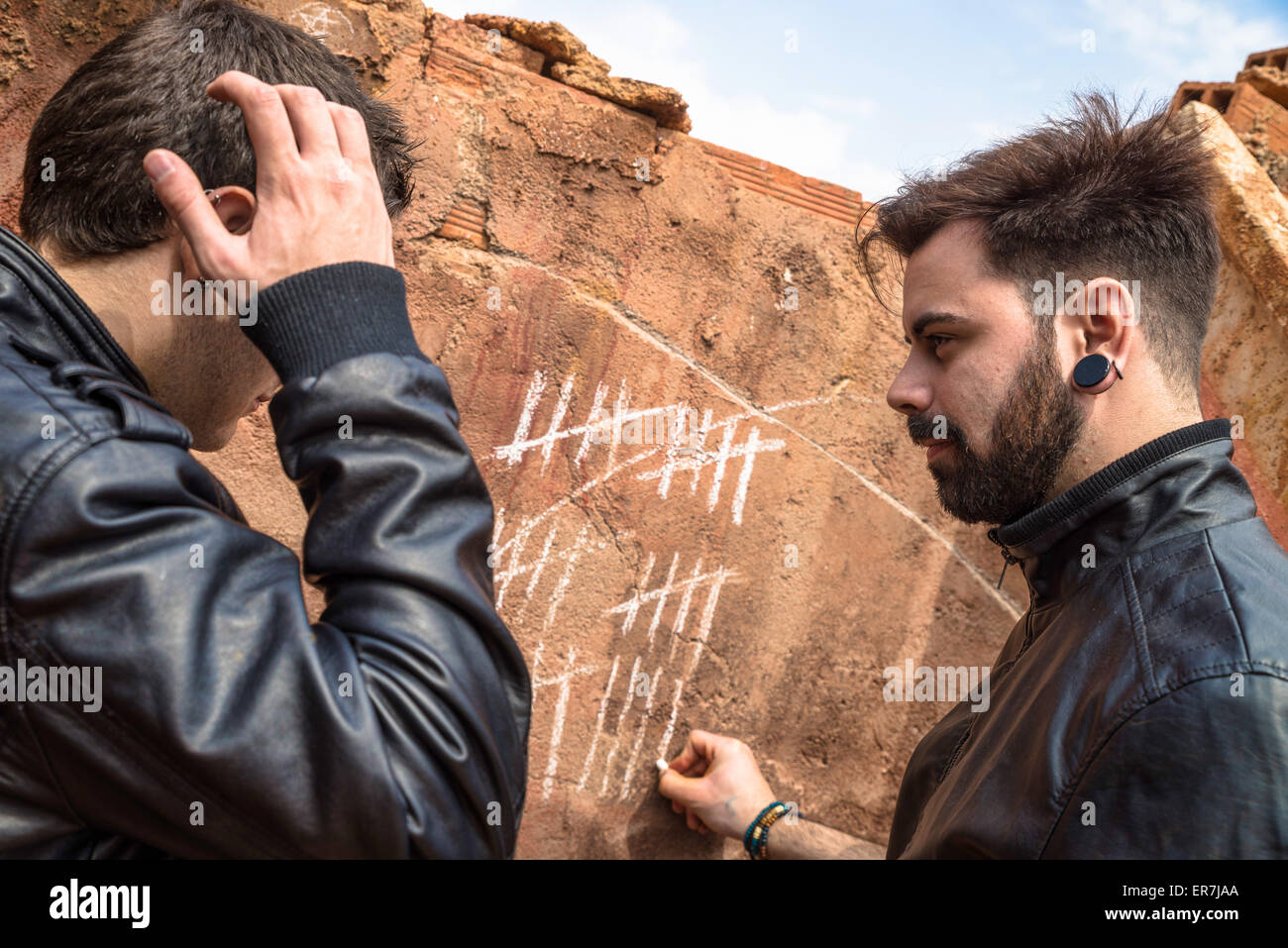 two guys counting days with chalk markings on a wall stock photo