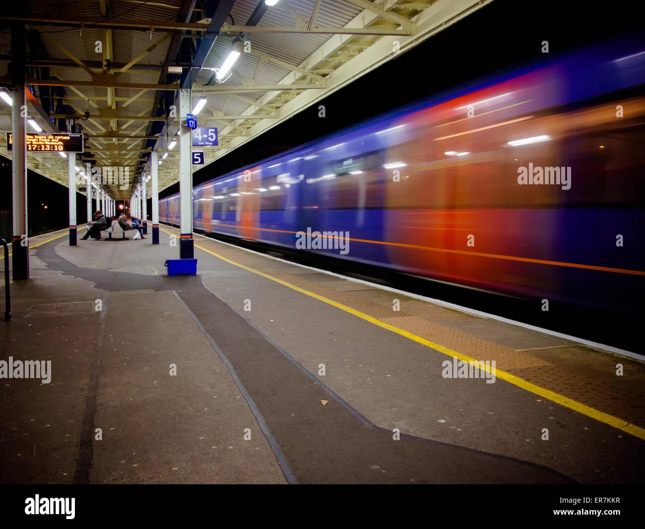 A train speeding through a train station - Stock Image