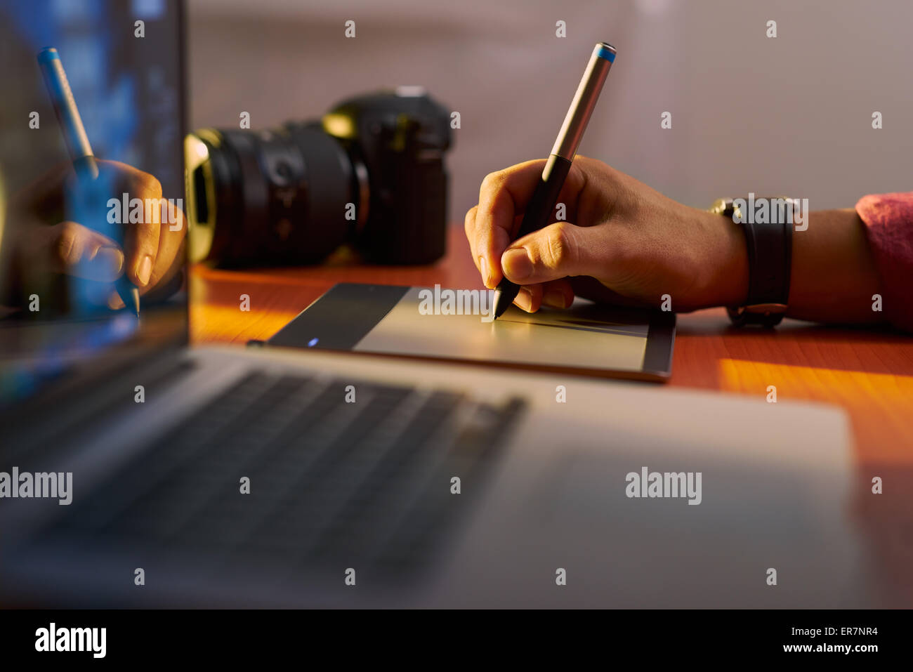 Photographer drawing and retouching image on laptop computer, using a digital tablet and stylus pen. Closeup of Stock Photo